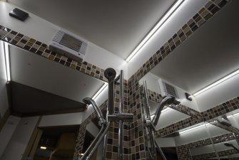 Koupelna se zrcadly a mozaikovými kachličkami.
