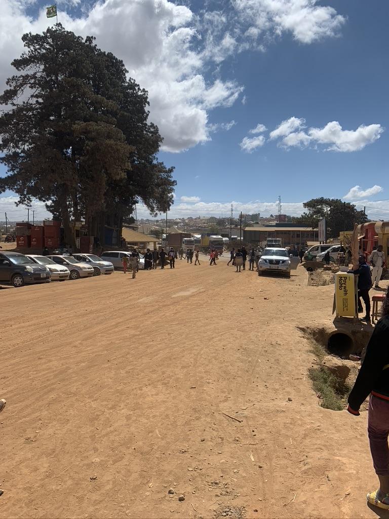 Pohled za Zambie na kamiony stojící na asfaltové silnici na tanzanské straně hranice.